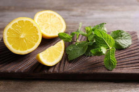 Cutting board with mint and lemon on wooden background 免版税图像 - 111088130