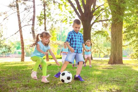 使用与球的逗人喜爱的小孩在公园