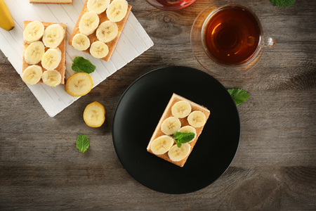 Plate with tasty banana cake and cup of tea on wooden table Stock fotó