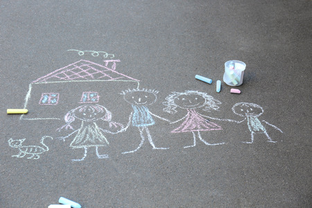 Chalk drawing of family and house on asphalt