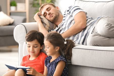 Cute children reading book while their father is sleeping on sofa at home Reklamní fotografie - 111298215