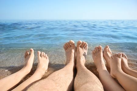 Legs of family resting at sea resort
