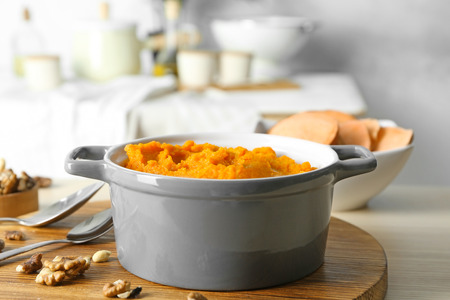 Mashed sweet potato in casserole pot on kitchen table