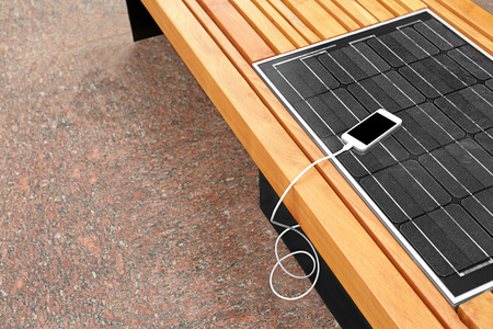 Mobile phone charging on bench with solar panel Banque d'images - 112186992