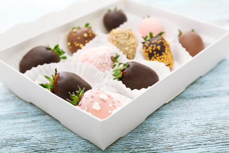 Box with tasty chocolate dipped and glazed strawberries on wooden background