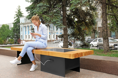 Young woman charging mobile phone on bench with solar panel Banque d'images - 112259505