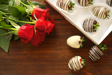 Box with tasty chocolate dipped strawberries and bouquet of flowers on table Stock Photo
