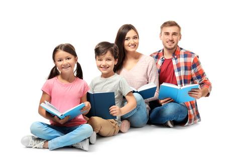 Happy family reading books on white background Фото со стока