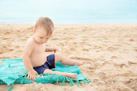 Cute boy sitting on beach Stok Fotoğraf