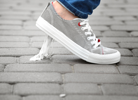 Foot stuck into chewing gum on street. Concept of stickiness Stock Photo
