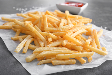 Yummy french fries on paper, closeup