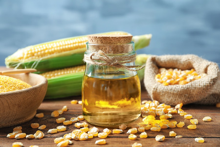 Glass jar with corn oil on table against blurred background