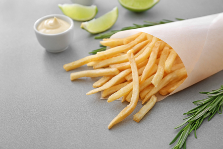 Paper cone with yummy french fries on table