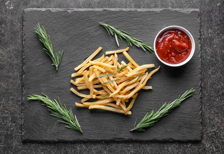 Yummy french fries on slate plate Фото со стока