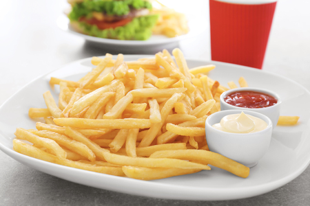 Plate with yummy french fries and sauces in small bowls on table Standard-Bild