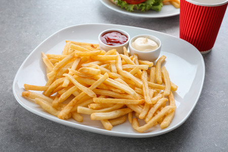 Plate with yummy french fries and sauces in small bowls on table Archivio Fotografico