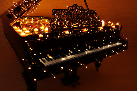 Vintage piano with Christmas lights and candles in dark room