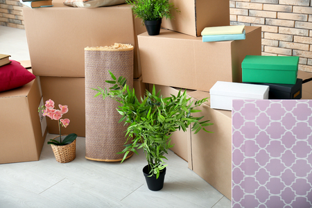Carton boxes and interior items on floor in room. Moving house concept Imagens