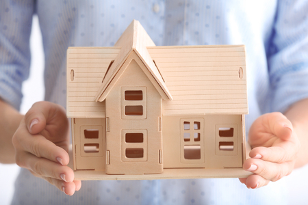 Woman holding wooden house, close up Stock Photo