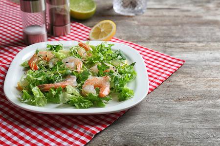 Plate with fresh tasty shrimp salad on table Stock Photo