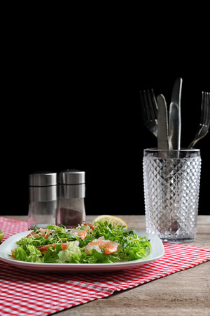 Plate with fresh tasty shrimp salad on table against black background Stock Photo