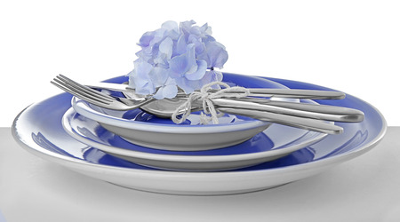 Ceramic dishware and cutlery on white background