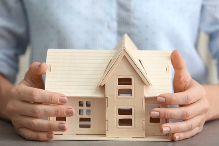 Woman holding wooden house at table, close up Stock Photo