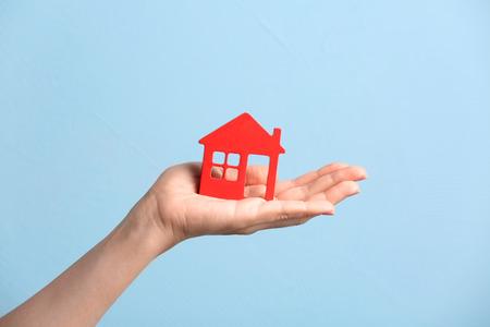 Woman holding wooden figure of house on color background Reklamní fotografie