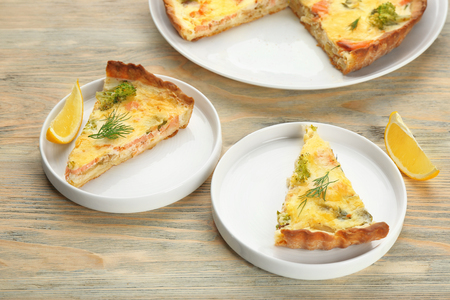 Plates with pieces of tasty salmon quiche on table