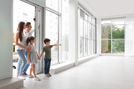 Familia feliz entrando en casa nueva