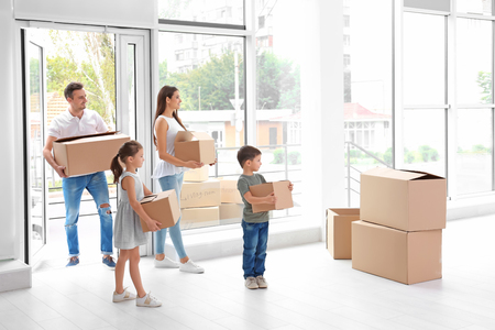 Happy family with moving boxes entering new house Stok Fotoğraf