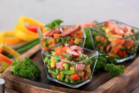 Vegetable salad with sausage in glass bowls on wooden board