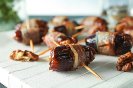 Wooden board with bacon wrapped dates, closeup 写真素材