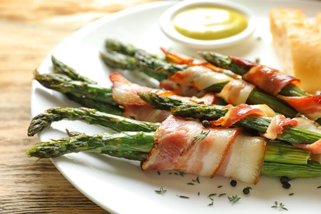 Plate with bacon wrapped asparagus on table, closeup 免版税图像