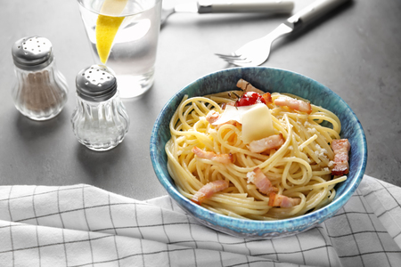 Bowl of pasta carbonara with bacon on table