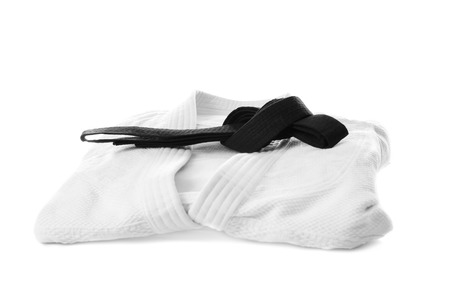 Karate uniform with black belt on white background