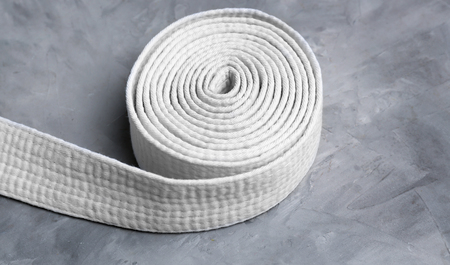 White karate belt on grey background