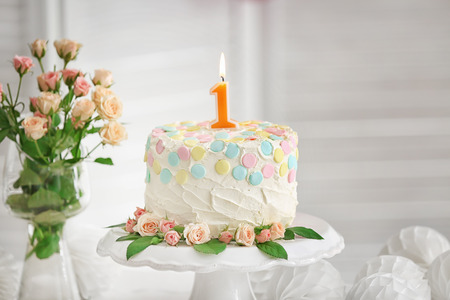 Cake with candle for first birthday on dessert stand
