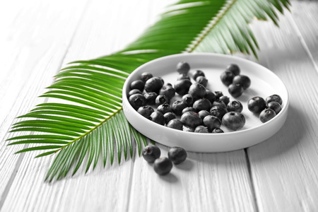 Plate with fresh acai berries and palm leaf on wooden table Stock Photo
