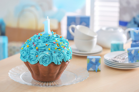 Cake with candle for first birthday on table