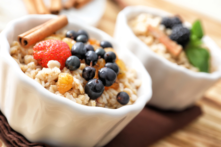 Tasty oatmeal with berries in bowl, close up Archivio Fotografico