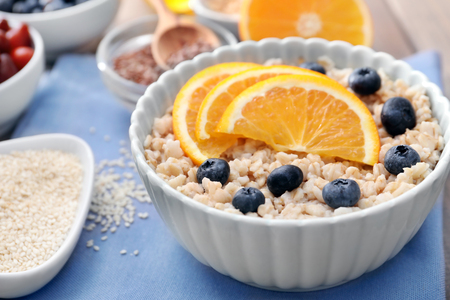 Tasty oatmeal with fruit in bowl on table Stock Photo