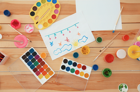 Set of paints, brushes and children's painting on wooden table Standard-Bild