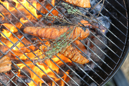 Tasty salmon slices on barbecue grill, close up Stock Photo
