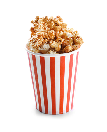 Cup with tasty caramel popcorn on white background Imagens