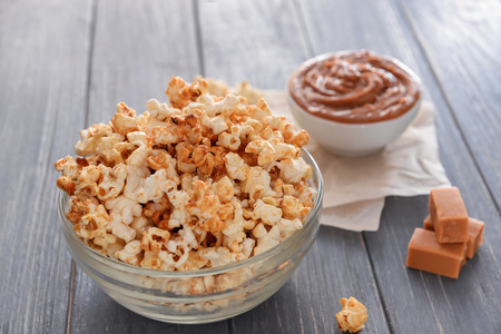 Bowl with tasty caramel popcorn on wooden table