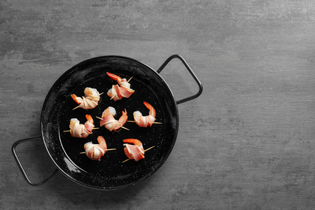 Frying pan with bacon-wrapped shrimps on table Banque d'images