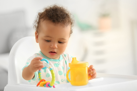 Cute baby with bottle of water sitting on chair indoors