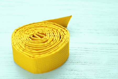 Yellow karate belt on wooden background Stock Photo