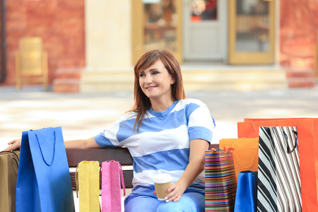 Attractive mature woman with shopping bags sitting on bench outdoors